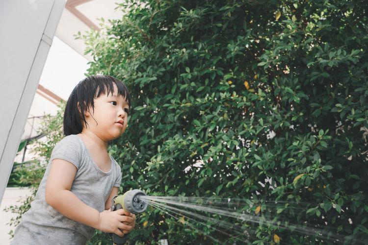 Cute girl watering plant outdoors