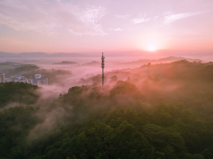 Aerial view of 5g communication tower during beautiful sunrise with clouds