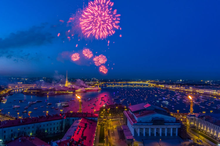 Firework display over river against buildings in city at night