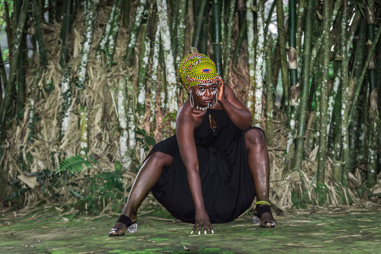 African woman sitting in front of bamboo forest with african face painting.