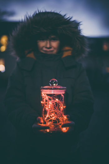 Boy with christmas lights in glass standing outdoors on street with winter coat and christmas lights in background Bokeh Boy Celebration Child Christmas Decoration Glass Hands Happy Holding Joyful Lights Night One Person Outdoors People Season  Winter