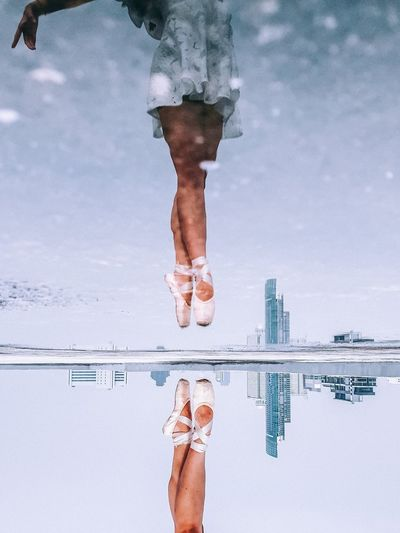 Low section of ballet dancer dancing while reflecting on puddle