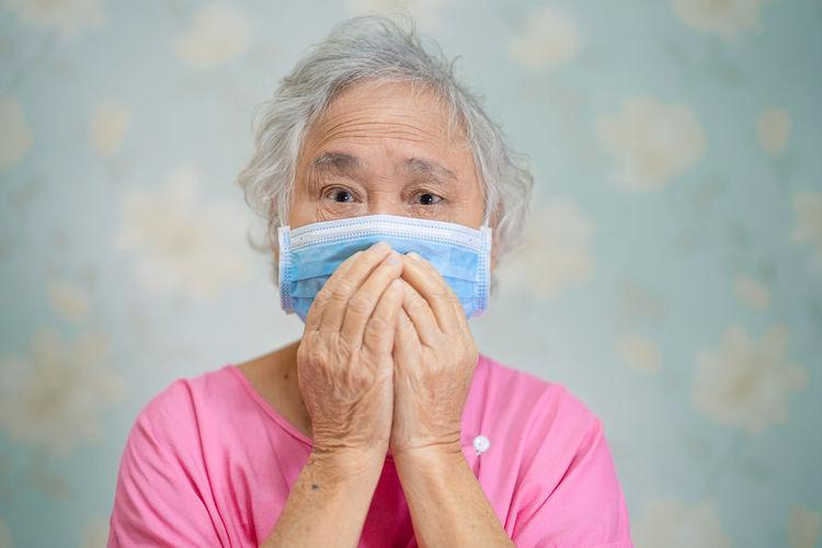 Portrait of senior woman wearing flu mask sitting at hospital