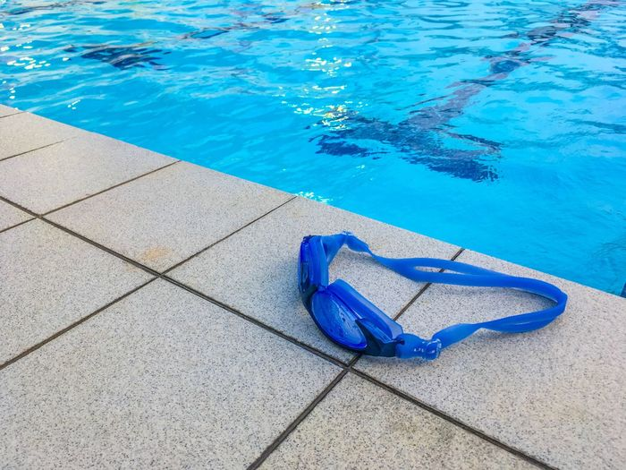 Blue swimming goggles at poolside