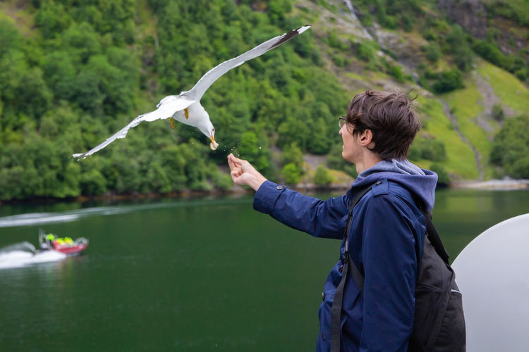 Young man feeding flying seagull while standing against lake