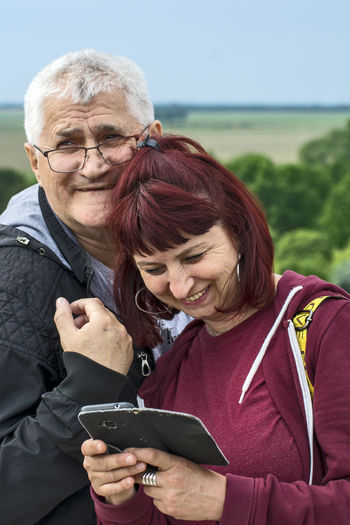 Portrait of smiling man with woman standing on smart phone