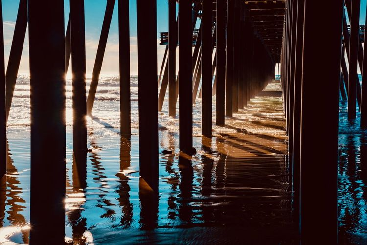 Water Reflection No People Sea Nature Tranquility Beach Day Beauty In Nature Tranquil Scene Outdoors Land Sunlight Architecture Wood - Material Sky Waterfront Built Structure Scenics - Nature Wooden Post Architectural Column Underneath