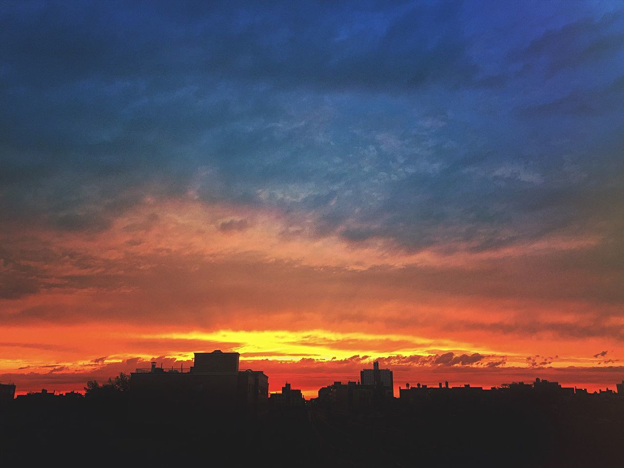 SILHOUETTE OF CITYSCAPE AGAINST CLOUDY SKY DURING SUNSET