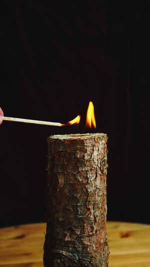 Close-up of burning candles on wooden table