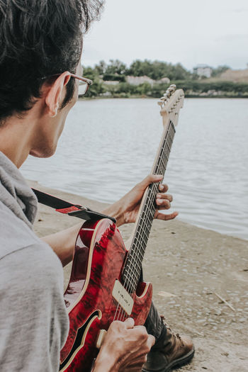 Man playing guitar on riverbank