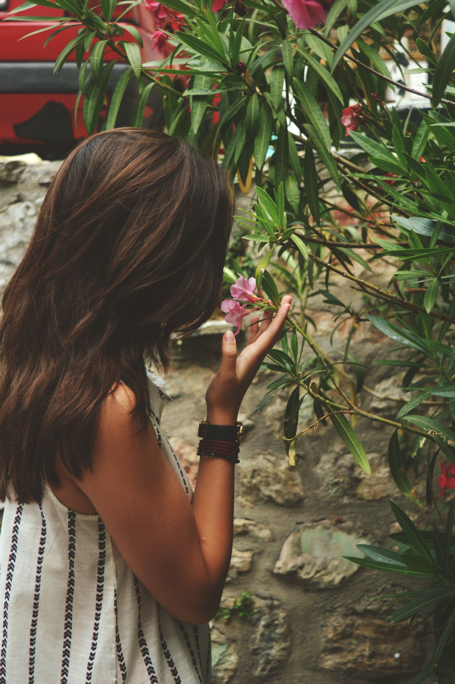lifestyles, side view, leisure activity, young women, person, young adult, looking down, long hair, casual clothing, growth, plant, medium-length hair, nature, outdoors, flower, day, green color, one woman only