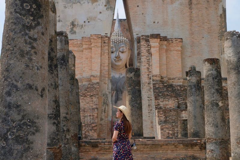 Woman standing by statue against building