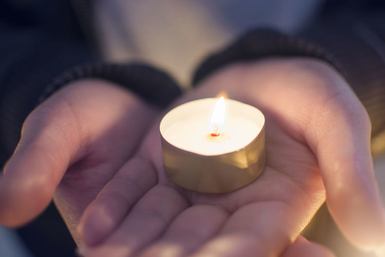 Close up hand of woman holding lighting candles in the palm at the church Burning Fire Candle Flame Hand Holding One Person Human Finger Lifestyles Human Hand Tea Light Finger Body Part Church Palm Candle Light Dark Frame Religion Truth Belive God Pray
