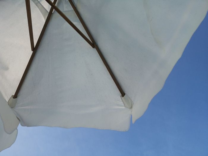 Low angle view of white umbrella against clear blue sky