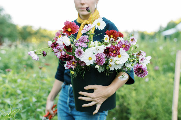 Midsection of woman standing by flowering plants on field