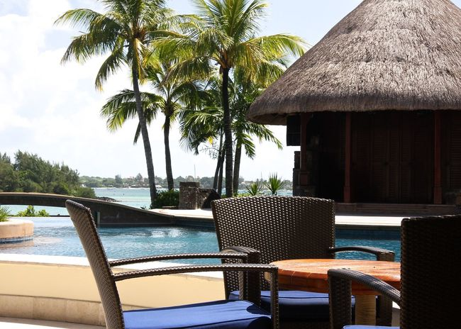 Architecture Beauty In Nature Blue Brown Chairs Enjoying Life Holiday Life Is A Beach Lifestyle Mauritius Nature Ocean Outdoors Palm Trees Pool Poolside Relaxing Restaurant Scenics Table Take Your Place Thatched Roof Tranquil Scene Travel Wineandmore