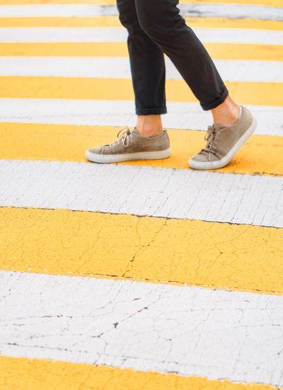 Low Section Body Part Road Marking Crosswalk Human Leg Zebra Crossing Human Body Part Marking Yellow Striped City Transportation Sign Symbol One Person Walking Shoe Crossing Road Men