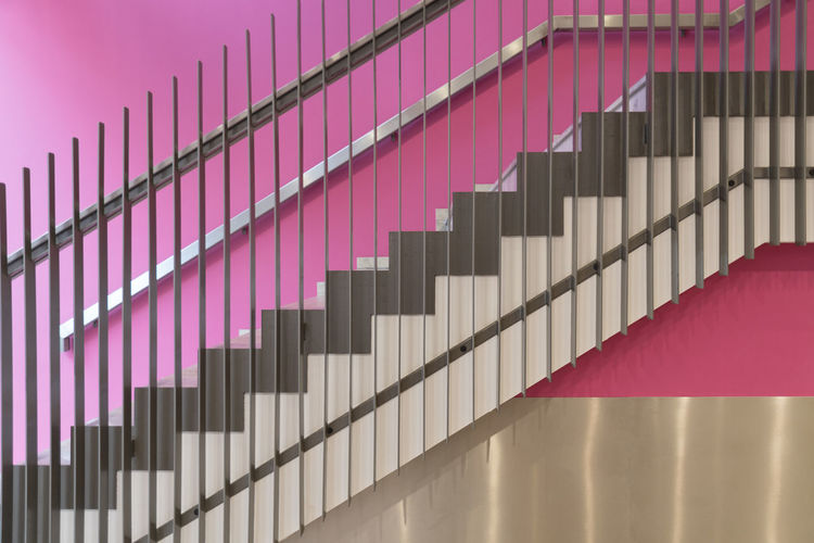 Low angle view of staircase by pink wall at home