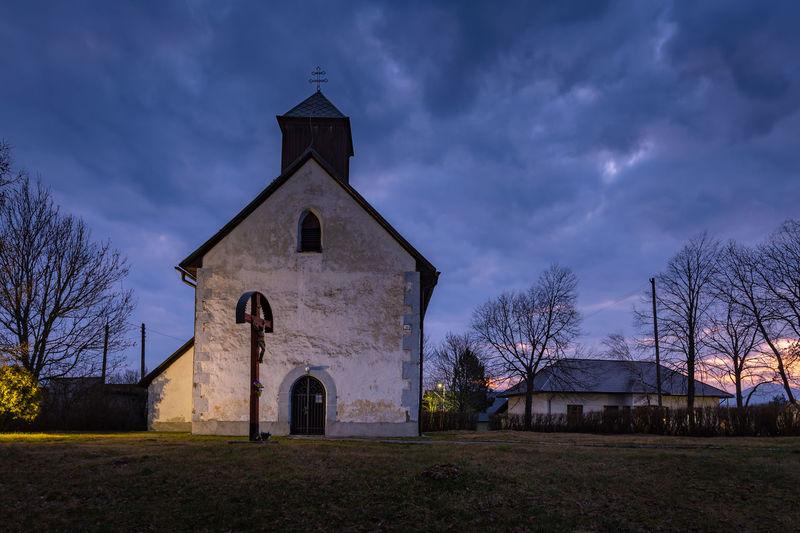Church by building against sky at dusk