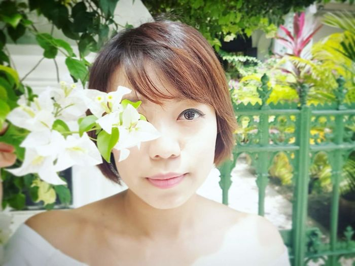 Close-Up Portrait Of Young Woman Standing By White Flowers Blooming Outdoors