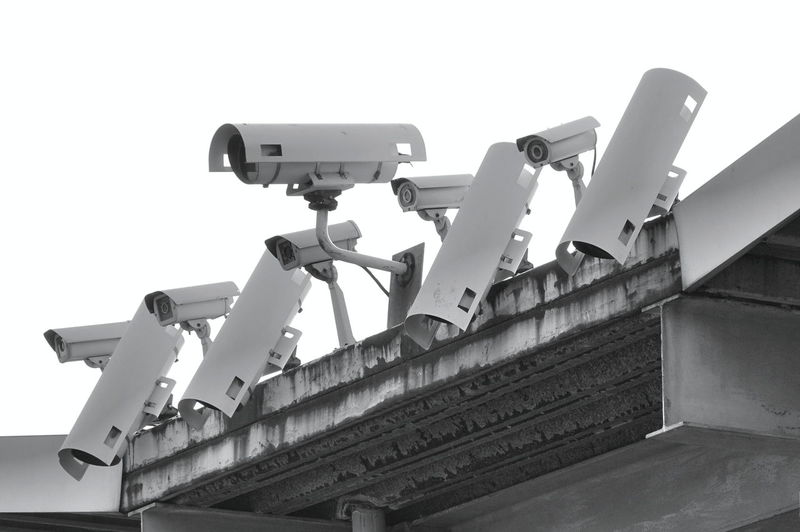 A row of security cameras keeps a watchful eye Security Camera Technology Security Surveillance Security System Monitoring Safety Observing Optics Video Camera Cctv Camera Cctv CCTV Security Monochrome