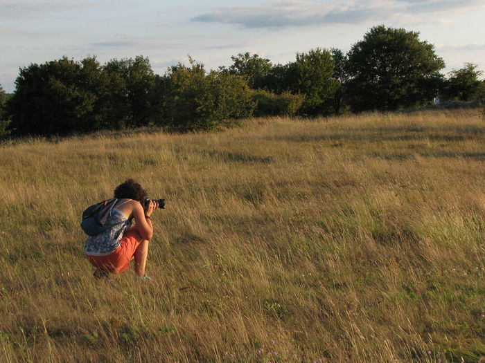 Woman Photographing On Field Against Sky