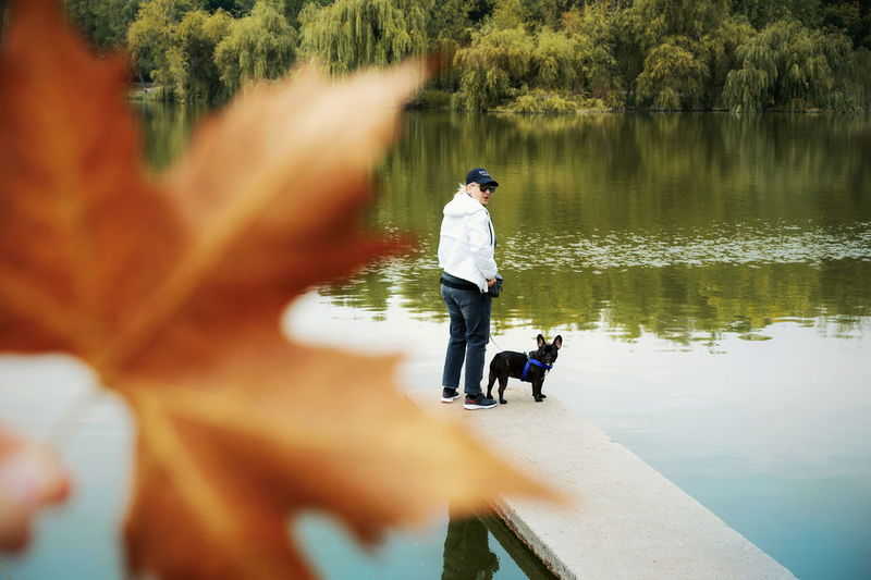 Full length of woman with dog standing on pier by lake