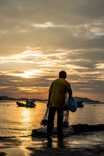 Fisherman with net at sea Escapism Fisherman Fishing Nets Fishing Time Folkwang Hobby Jetty Job Light Man Net Outdoors Port Sea Silhouette Sky Sky And Clouds Sun Sunset Sunset Silhouettes Sunset Tine Time Wave Web Wet