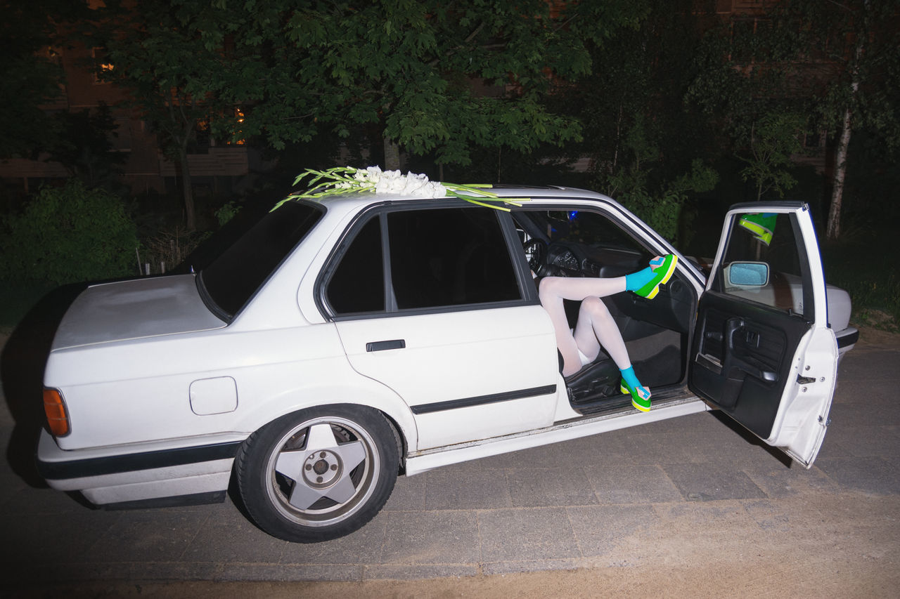 Low section of woman relaxing in car at night