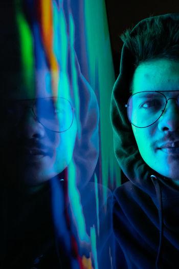 Portrait of man wearing eyeglasses in darkroom