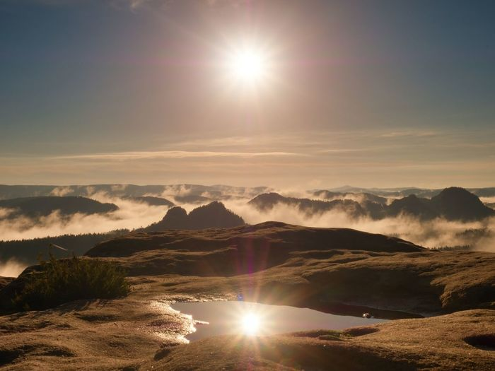 Water pool on cracked mountain summit. fairy daybreak in beautiful hills. peaks of hills in mirror