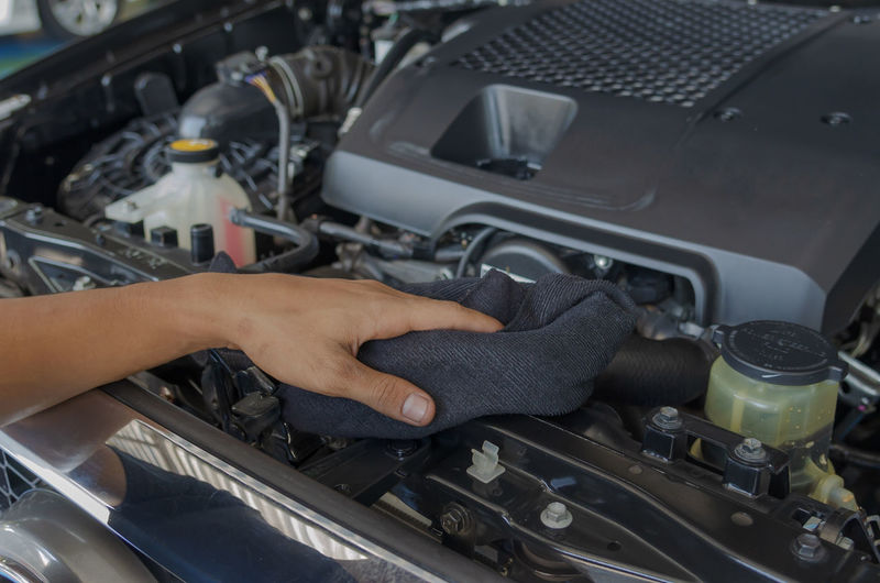 Cropped hands of man cleaning car with towel in garage