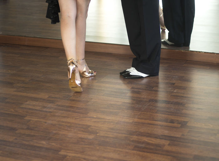 Low section of couple standing on hardwood floor