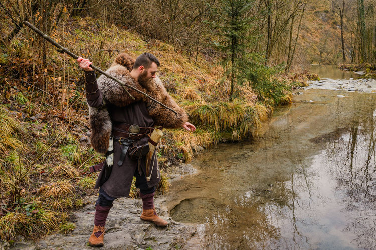 Full length of warrior hunting with stick in river