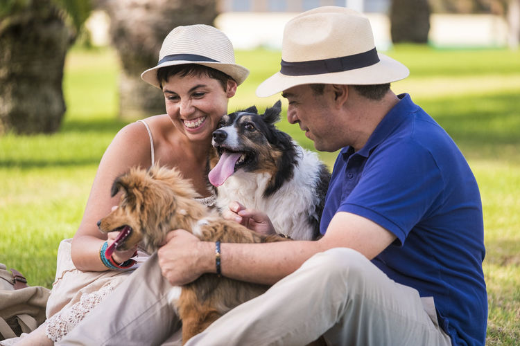 Smiling couple with dogs sitting on grassy field in park