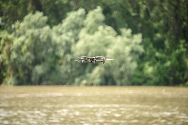 Airplane flying over river against trees