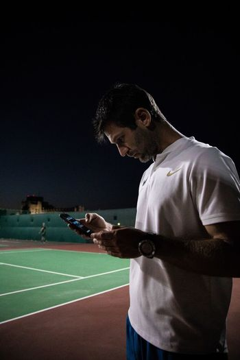 He is texting on the tennis court. Sport Real People People Athlete Night Men Sportsman Clothing Adult Standing
