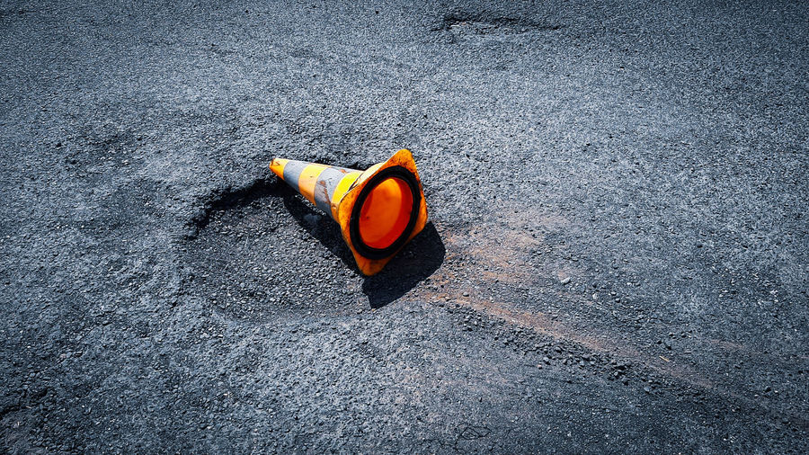 High angle view of orange traffic cone by hole on road