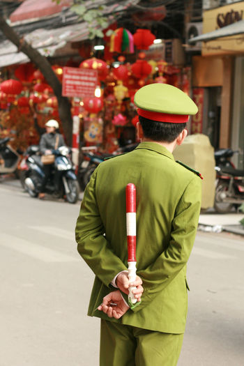 Rear View Of Security Guard Holding Baton Standing On Street