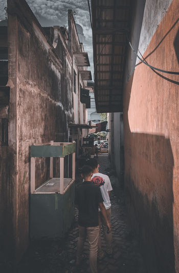 Rear view of woman standing on alley amidst buildings