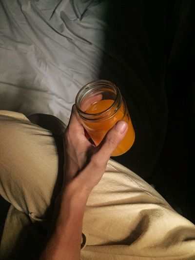 Hand holding orange juice in a small glass jar