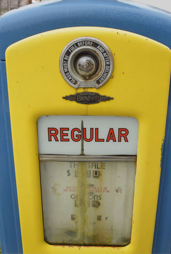 faded yellow and blue paint on vintage gas pump Close-up Communication Day Gas Pump Information Sign No People Outdoors Retro Design Retro Styled Text Text Vending Machine Vintage Yellow