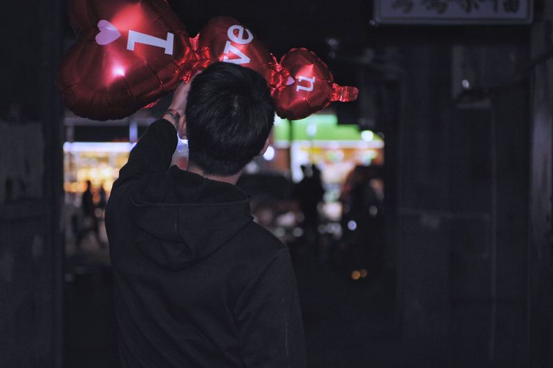 Rear view of man on touching decoration outdoors at night