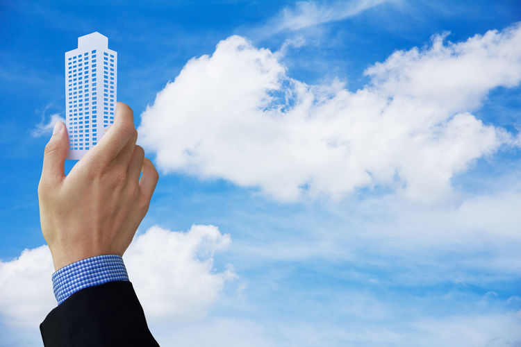 Cropped of business person holding model building against cloudy sky