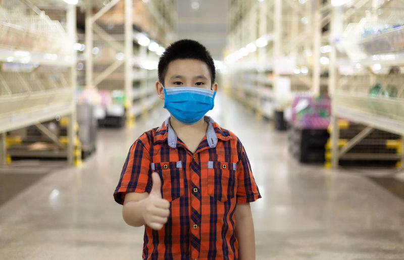 Portrait of cute boy with mask showing thumb standing in factory