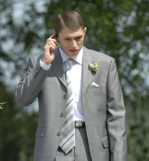 Bridegroom talking on mobile phone while standing outdoors