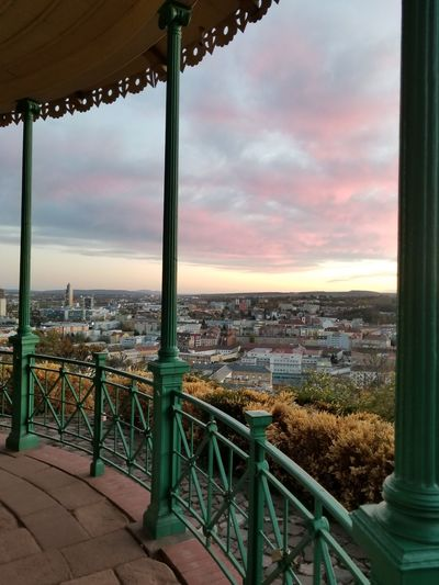 A view of pink clouds as seen from a gazebo overlooking the city. City View  Overlook Evening Sky Evening Light Autumn Colorful Garden Serene Europe Czech It Out Bushes Gazebo Architecture Structure Park - Man Made Space Hand Rail Decorative Wrought Iron Design Curve Pillars Pink Clouds Perspective Horizon City Cityscape Sunset Urban Skyline Multi Colored Sky