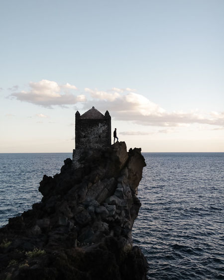 Alone Time Santa Tecla Sicilia Sicily Silhouette Standing Wanderer Wanderlust Beauty In Nature Cliff Lost In The Landscape Clouds And Sky History Horizon Horizon Over Water Nature On The Top Outdoors Rocks Scenics Shore Standing Still Sunset Tower Tranquility