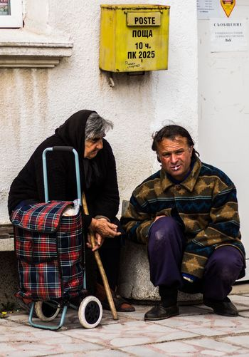 Homeless man crouching by senior woman in city