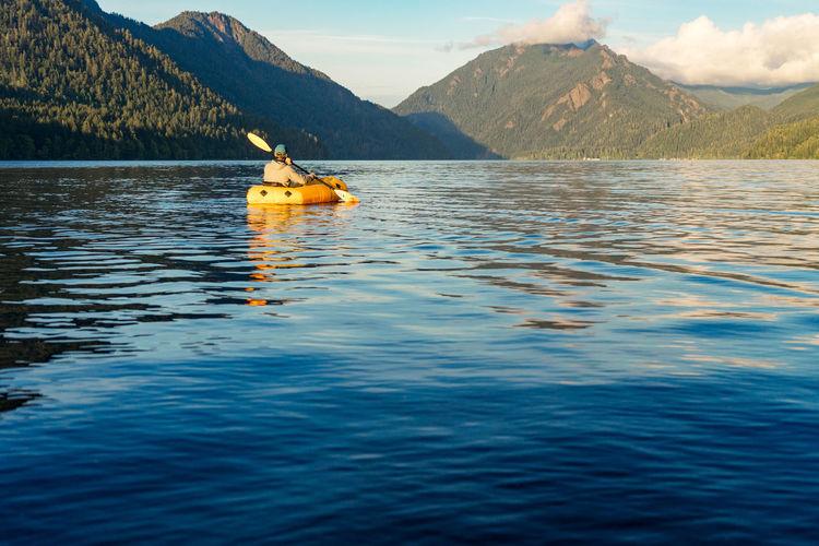Boat in lake against mountain range